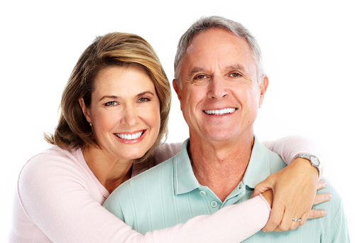 An older man and woman smiling and hugging