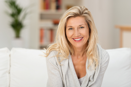 A middle aged woman sitting on a couch smiling